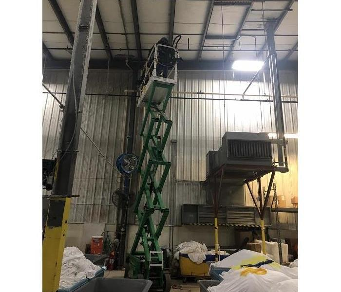 Photo of crew member cleaning high walls in warehouse