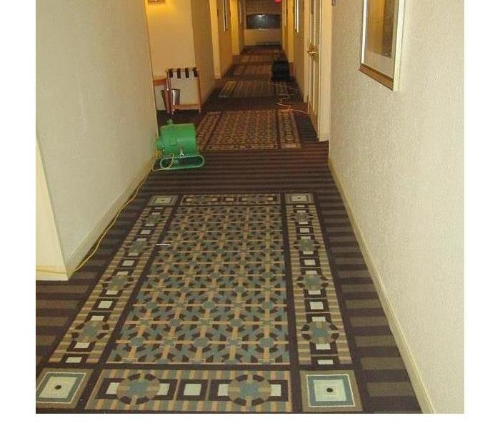 long hotel hallway, with colorful carpeting being dried out by SERVPRO equipment