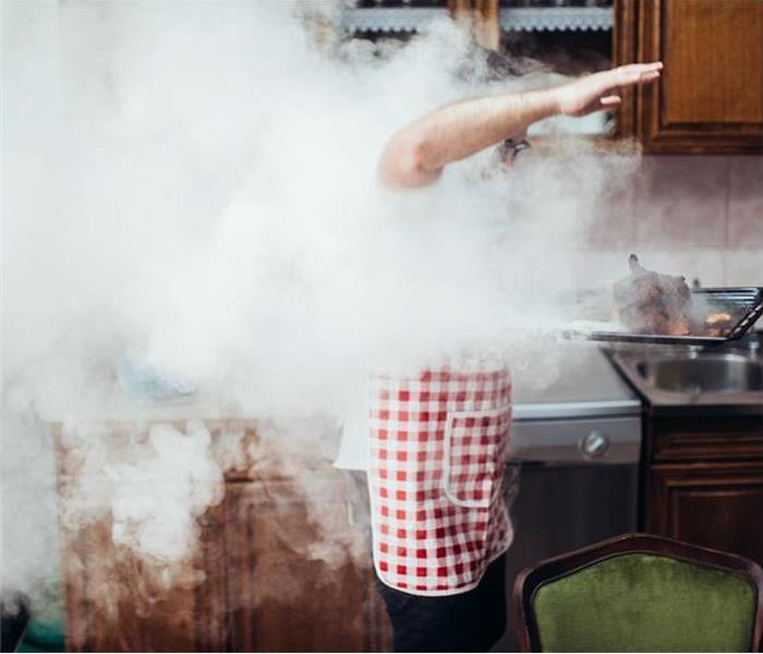 Man in smoky kitchen holding burning food