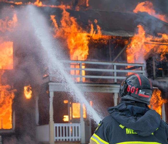 Photo showing house engulfed in flames with fireman attempting to put out