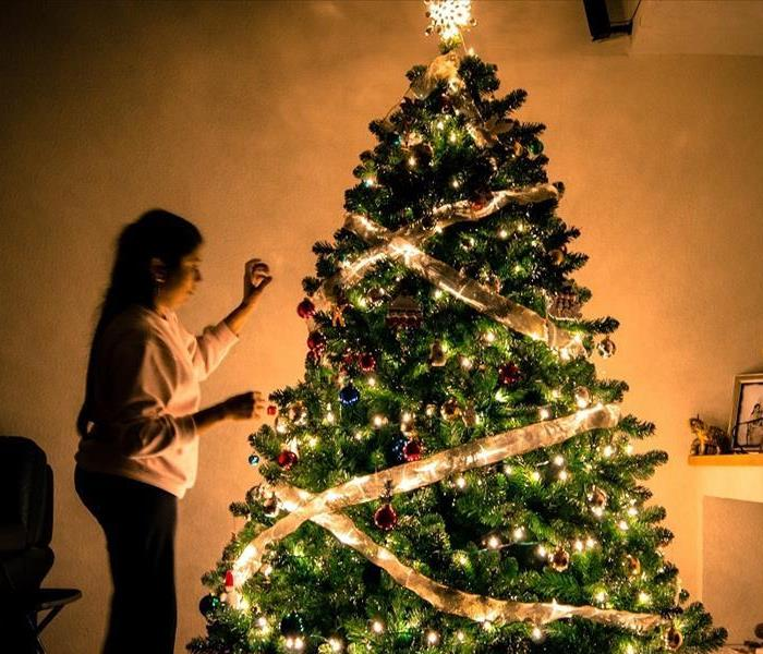 Photo of woman decorating Christmas Tree